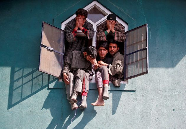 People react as they sit in a window of a mosque during the funeral of Tauseef Ahmad Wagay, a suspected...