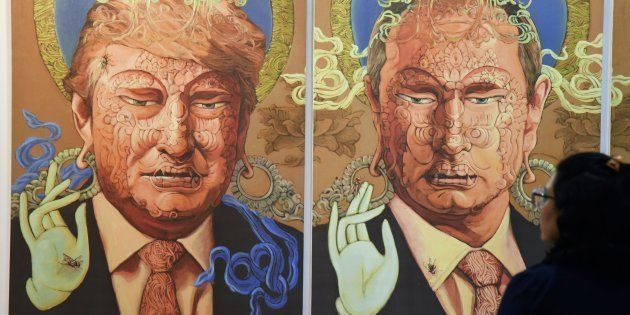 A visitor looks at a painting representing US President Donald Trump (L) and Russian President Vladimir...