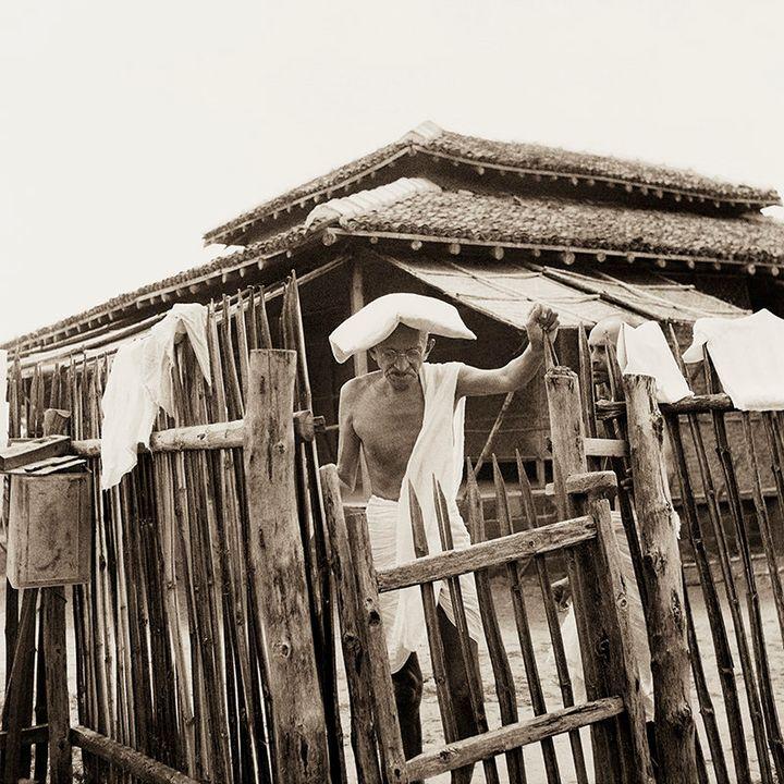 Mahatma Gandhi in front of his office hut, Sevagram Ashram, 1940.