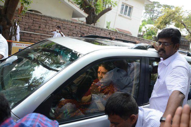 Indian Anna Dravida Munnetra Kazhagam (AIADMK) party leader V.K. Sasikala gestures to party members and...