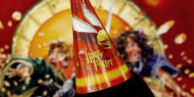 Mumbai, INDIA: A young Indian Harry Potter fan strikes a pose in front of a Harry Potter poster inside...