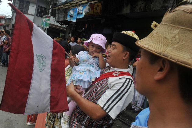 An ethnic Lepcha toddler holds a flag while waiting for the arrival of India's West Bengal state Chief...