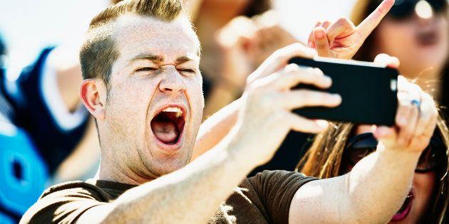 Man celebrating in stadium at football game taking selfie with