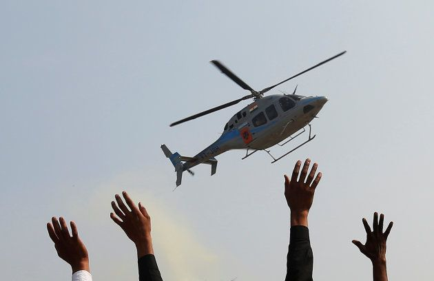 Supporters wave towards a helicopter carrying Keshav Prasad Maurya, the Uttar Pradesh state's president...