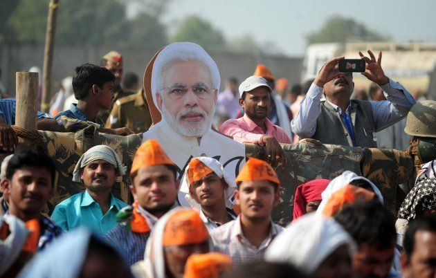 Supporters of India's Bharatiya Janata Party (BJP) listen to BJP Leader and Indian Prime Minister Narendra...
