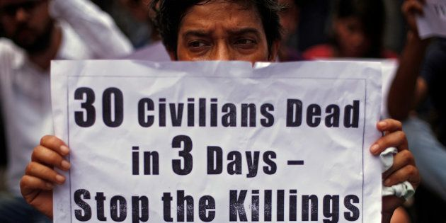 A woman holds a placard as she attends a protest against what they say are the recent killings of Kashmiri...