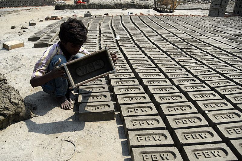 "Pawan Kumar (name changed) moulds up to 200-300 bricks a day. When I asked how old he is, he shrugs and turns to his parents. ""About 13 or 14,"" replies his mother."