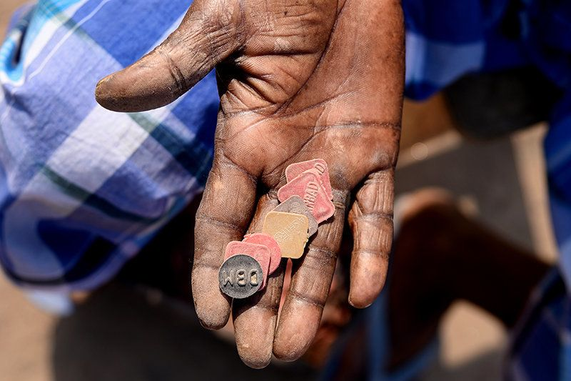 A worker counts tokens—he will get paid at the end of day based on how many of these he has. The workers' daily wages are based on the number of bricks made or carried.