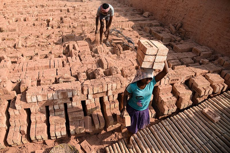 Barefoot girls carrying burnt bricks to the factory area. Atindra Nath Das, regional director (East),...