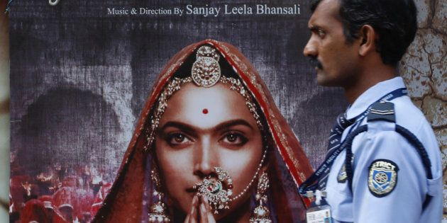 A security guard walks past a poster of the upcoming Bollywood movie 'Padmavati' outside a theatre in...
