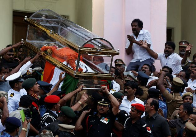 People cry as the body of Tamil Nadu Chief Minister Jayalalithaa Jayaraman is carried during her funeral...