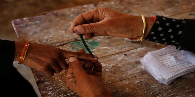 A woman gets her finger inked before casting her vote at a polling station during the state assembly...