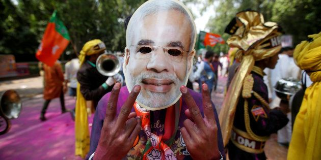 A supporter of India's Bharatiya Janata Party (BJP) celebrates after learning of the initial poll results...