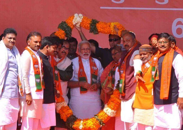 Prime Minister Narendra Modi waves at the crowd during a visit to Khushipur on March 6, 2017 in Varanasi,