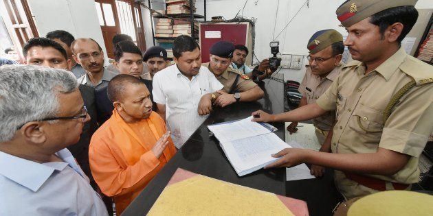 UP Chief Minister Yogi Adityanath speaks to a police personnel during a surprise visit at the Hazratganj...