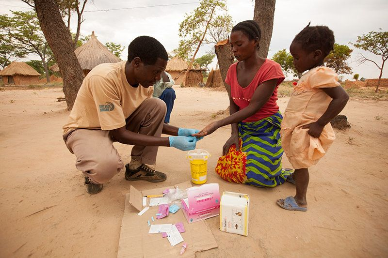 A community health worker administers a rapid diagnostic test on a mother and child for malaria.