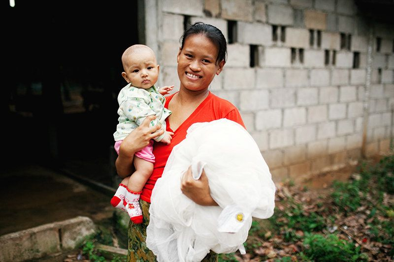 A mother and her young child receive a mosquito net to prevent malaria transmission in Thailand. Pregnant women and children under five are most vulnerable to malaria.