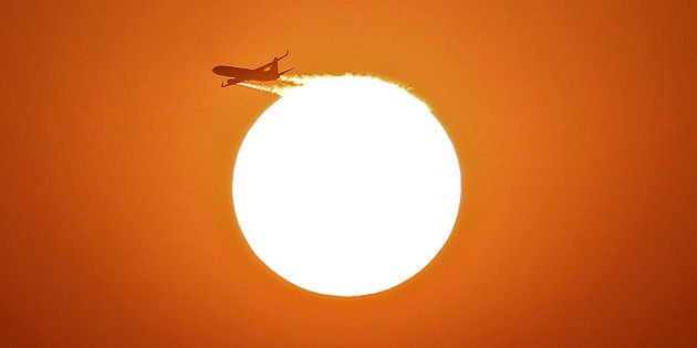 An aircraft files near the setting sun in New Delhi November 30,