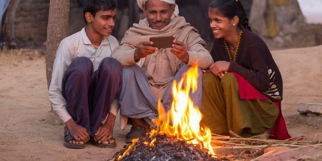 India, Uttar Pradesh, Agra, village man and his two children looking at photos on a smartphone by open