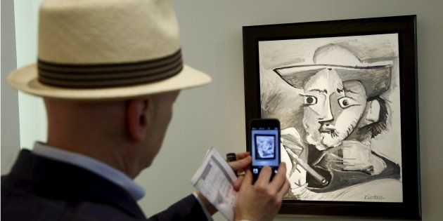 A man takes a picture of the painting