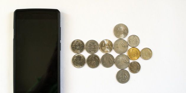 Arrow of coins from mobile phone. Mobile phone with indian currency set on a white background. Denoting...