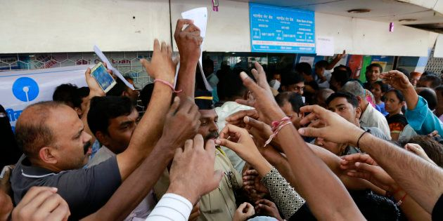 Indians stretch out their hands to collect withdrawal slips from a police officer to deposit and exchange...