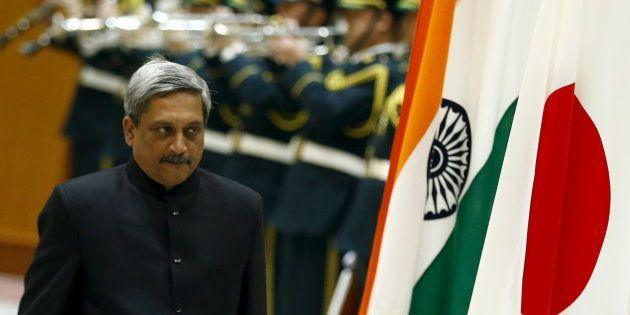 Indian Defense Minister Manohar Parrikar walks past the Indian and Japanese flags as he inspects the...