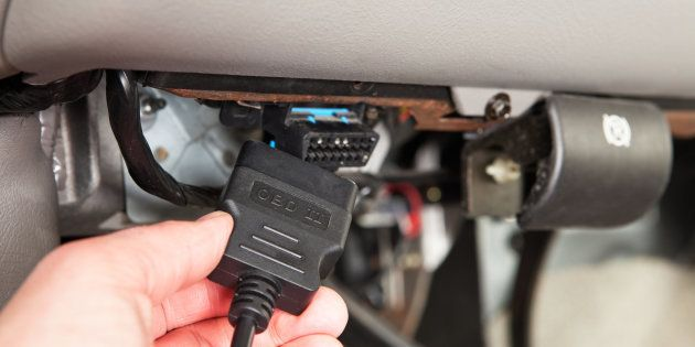 Mechanic Connecting OBD Scanner below SUV