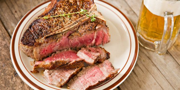 File photo of a thick, partially sliced porterhouse house stake done rare and a glass mug full of ice...