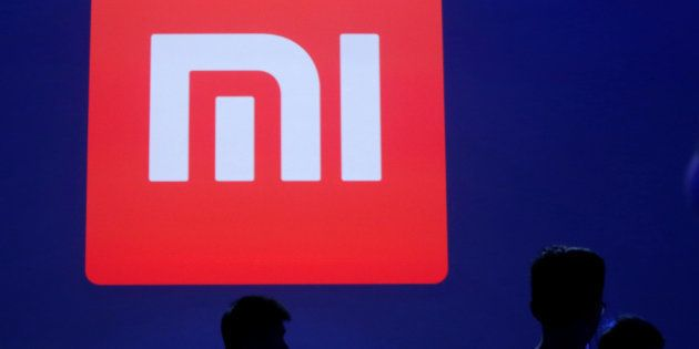 Attendants are silhouetted in front of Xiaomi's logo at a venue for the launch ceremony of Xiaomi's new...
