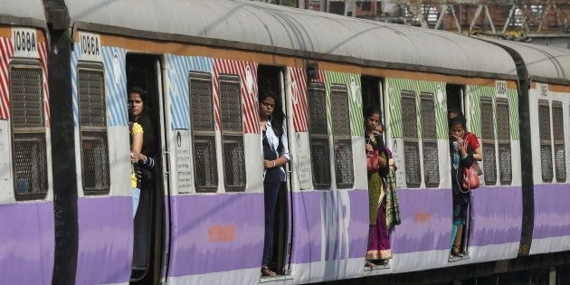 Commuters stand on the doors of a suburban train as it approaches the Churchgate railway station in Mumbai,...