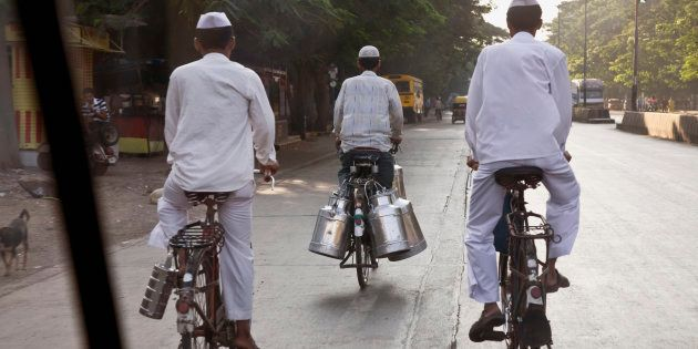 India, Mumbai, two delivery service men (dabbawallahs), and a milkman, riding on bicycles, rear