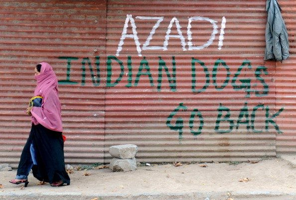 A Kashmiri woman walks past grafitti that reads