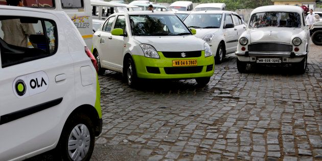 In this March 29, 2016 photo, Ola cabs, left, waiting for customers are parked next to other cars in...