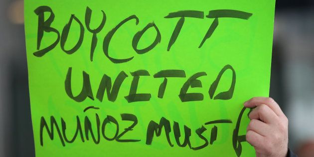 Demonstrators protest outside the United Airlines terminal at O'Hare International Airport on April 11,...