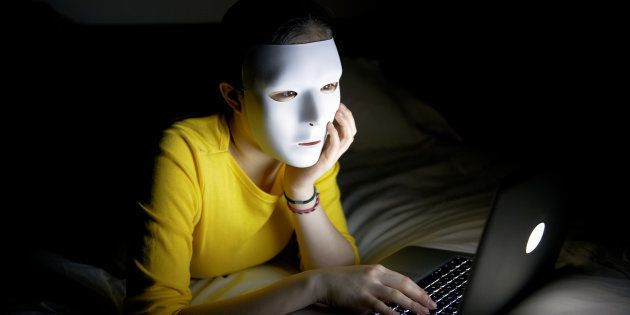 Anonymous teenager in mask on internet at