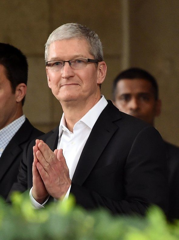 Apple chief executive Tim Cook greets onlookers as he leaves the Taj Mahal Palace hotel in Mumbai on...
