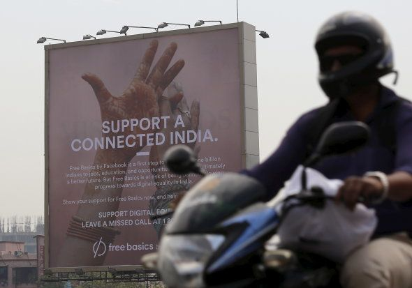 A motorist rides past a billboard displaying Facebook's Free Basics initiative in Mumbai, India, December...