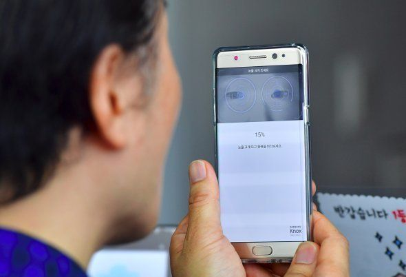 A South Korean man sets up iris recognition function on his replacement Samsung Galaxy Note7 smartphone...