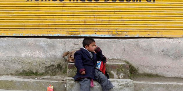 A Kashmiri school boy waits for a bus by a road side in Srinagar March 13,