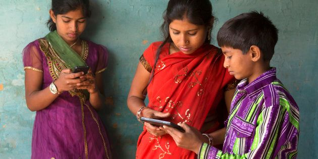 Indian brother and sisters using smartphone and tablet