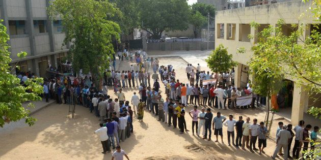 NEW DELHI, INDIA APRIL 23: Voters line up at a polling booth to cast their vote for MCD polls at Tuglakabad,...