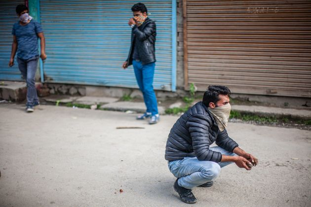 SRINAGAR, KASHMIR, INDIA - MAY 04: Kashmiri student throw stones at Indian government forces, during...