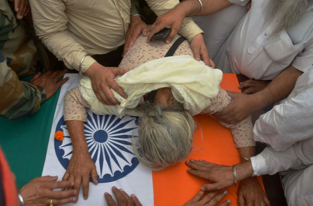 Gurinder Kaur, the mother of Indian Army soldier Paramjeet Singh cries over his coffin during his funeral...