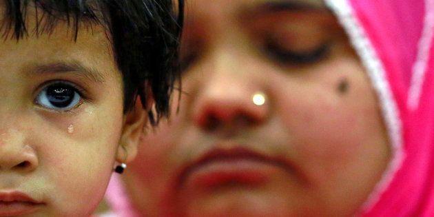 Aksha Yakub Rasool, 2, sits on her mother Bilkis Bano's (R) knee during a press conference in New Delhi,...