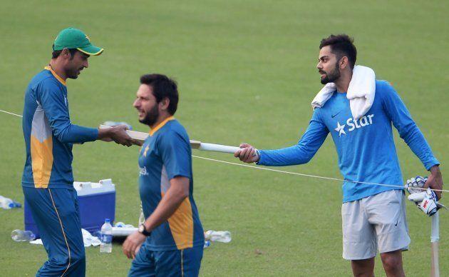India's Virat Kohli (R) presents a cricket bat to Pakistan's Mohammad Amir (L) as Pakistan's captain...