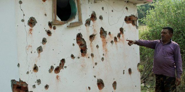 Jammu: A villagers points out damaged wall of a house after mortal shelling from Pakistan, at Jhanghar...