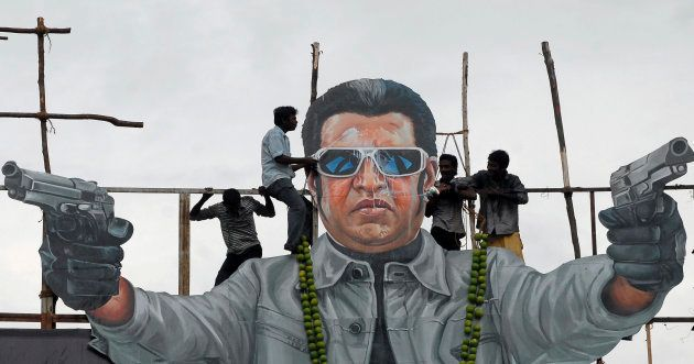 Fans of south Indian film star Rajinikanth pour milk as an offering over his cut-out on the release date...
