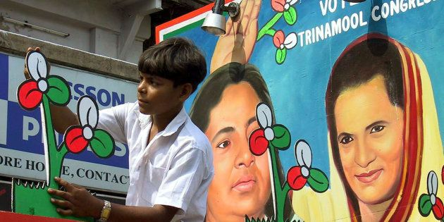 An Indian boy gives the finishing touches to the symbol of the regional Trinamool Congress party in front...