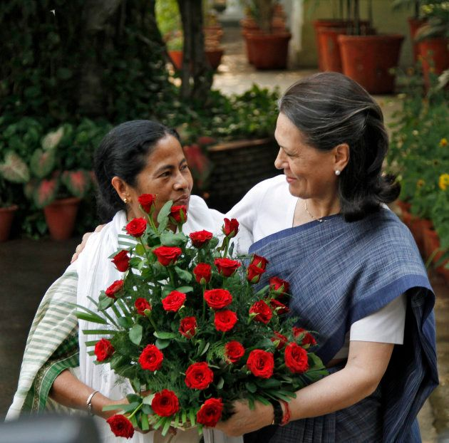 Trinamool Congress (TMC) chief Mamata Banerjee (L) presents a flower bouquet to chief of India's ruling...